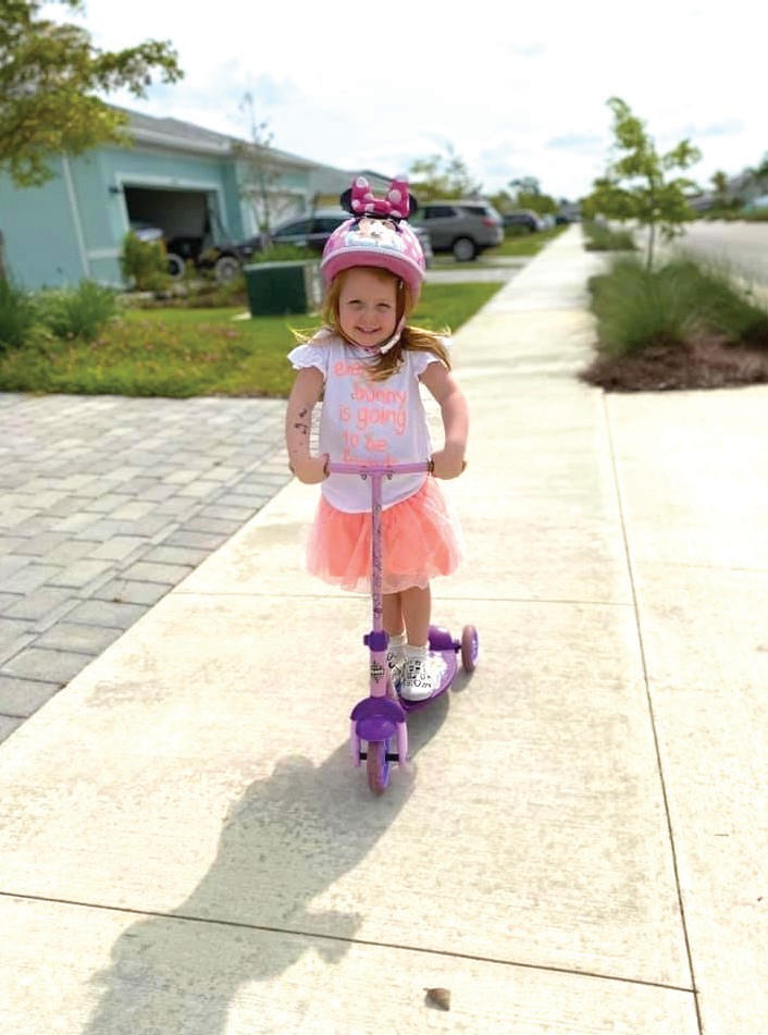 Atlantis Caissie rides a scooter down the sidewalk in her Babcock Ranch neighborhood. COURTESY OF JASON CAISSIE